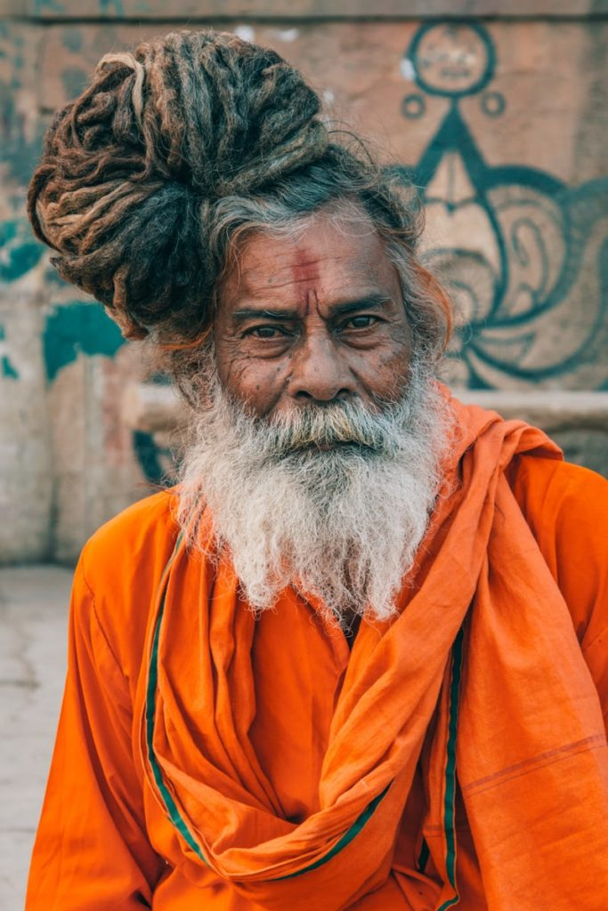 A yogi Baba In saffron clothes on the ghat of Ganges.